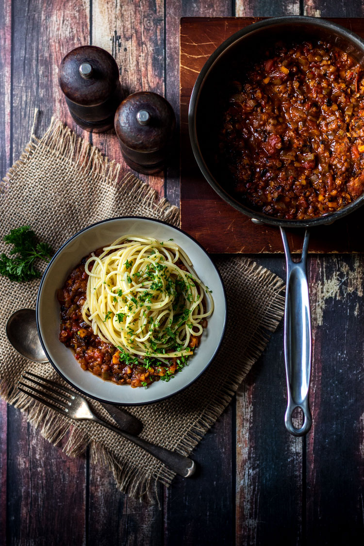 Overhead photograph of mushroom and lentil vegan spaghetti bolognese, served in a bowl.